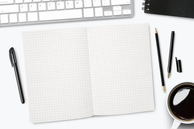 Leere gitterlinien notizbuchseite auf weißem schreibtisch.