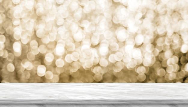 Leere glänzende tischplatte aus hellgrauem marmor mit verschwommenem funkelndem gold-bokeh-abstrakten hintergrund