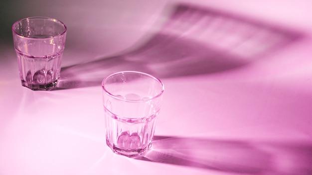 Leere gläser mit dunklem schatten auf rosafarbenem hintergrund