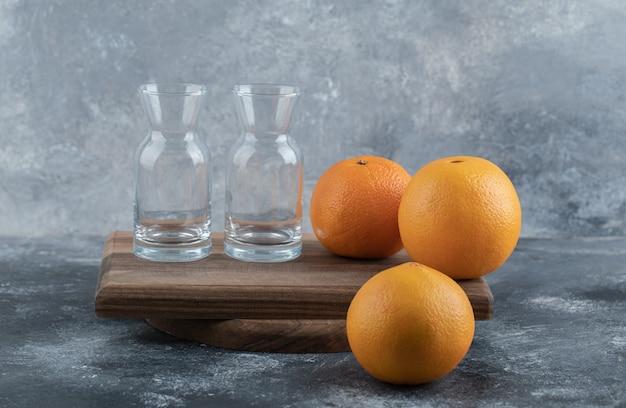 Leere gläser und frische orangen auf holzbrett.