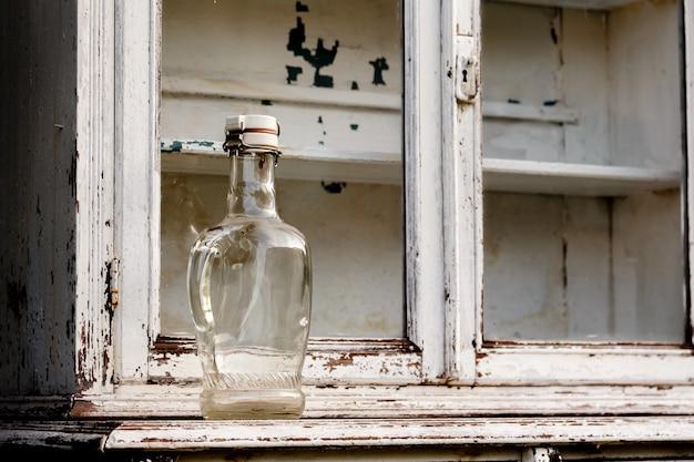 Leere glasflasche auf einem alten weißen küchenschrank