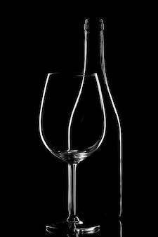 Leere glasflasche mit glas lokalisiert auf einem schwarzen hintergrund