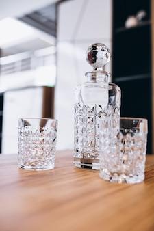 Leere glasflasche mit zwei gläsern