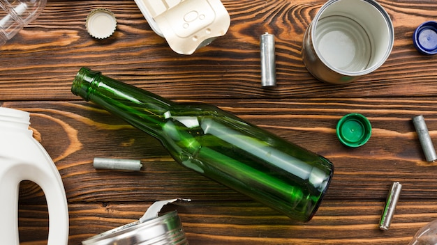 Leere glasflasche neben verschiedenem müll