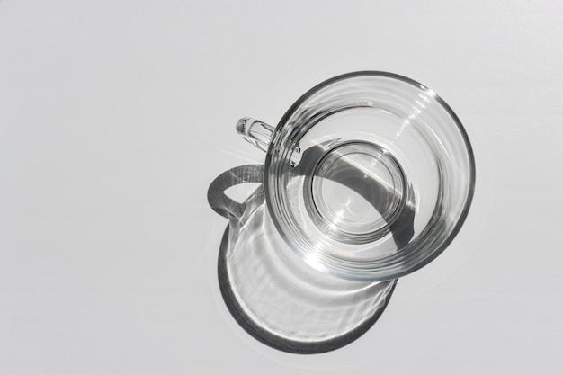 Leere glasschale auf weißem tisch mit sonnenstrahlen und schatten-draufsicht. licht durchdringt das geschirr.
