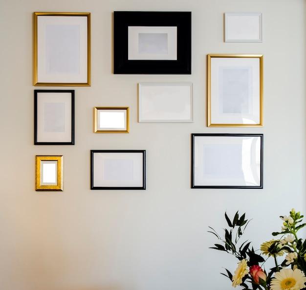 Leere goldene und schwarze foto- und bilderrahmen auf weißer wand für ihre fotos oder textkopien