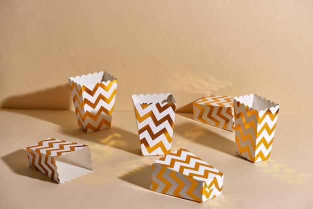 Leere goldene weihnachtstassen aus papier für winterferientreffen mit freunden mit neujahrsweihnachtsdekor auf beigem hintergrund