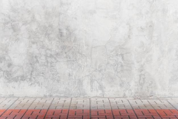 Leere graue betonmauer mit ziegelsteinboden im raum