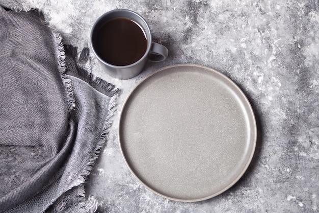 Leere graue platte und tasse kaffee
