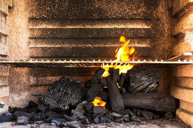 Leere grillgrube mit heißen holzkohlebriketts
