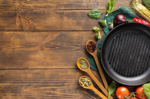 Leere grillpfanne mit frischen vegetarischen verschiedenen zutaten zum kochen von veganen grillgerichten über kopf