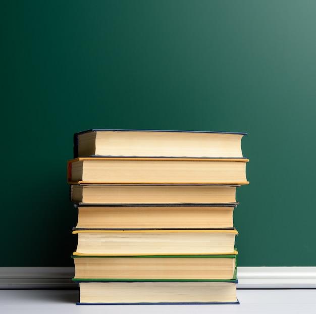 Leere grüne kreide-schulbehörde und stapel bücher, zurück zur schule, kopierraum