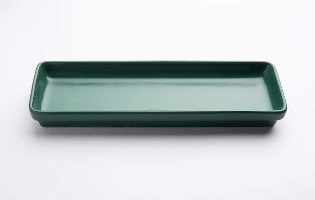 Leere grüne rechteckige keramikplatte isoliert auf weißem hintergrund