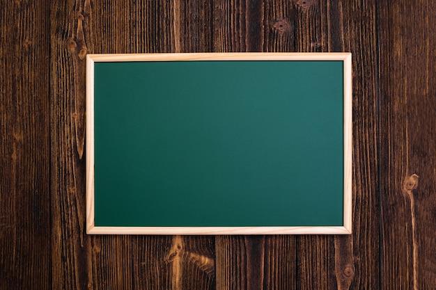 Leere grüne tafel mit holzrahmen auf hölzernem schreibtisch