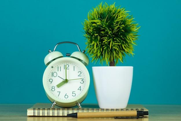 Leere grüne tafel und kleiner baum mit weinlesewecker und notizbuchpapier