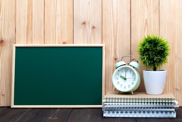 Leere grüne tafel und kleiner baum mit weinlesewecker