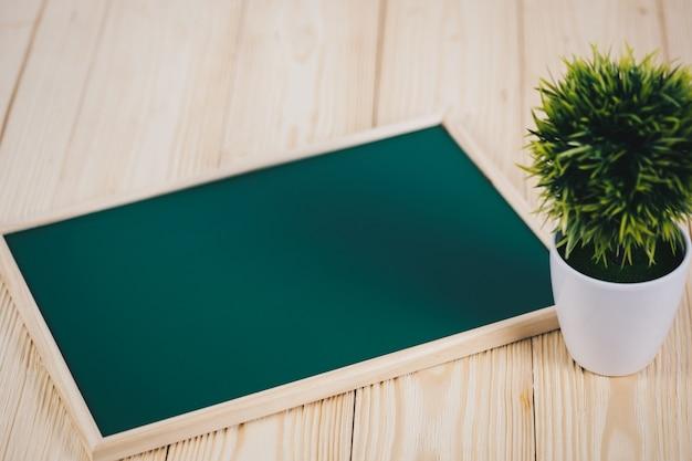 Leere grüne tafel und kleiner dekorativer baum auf holz