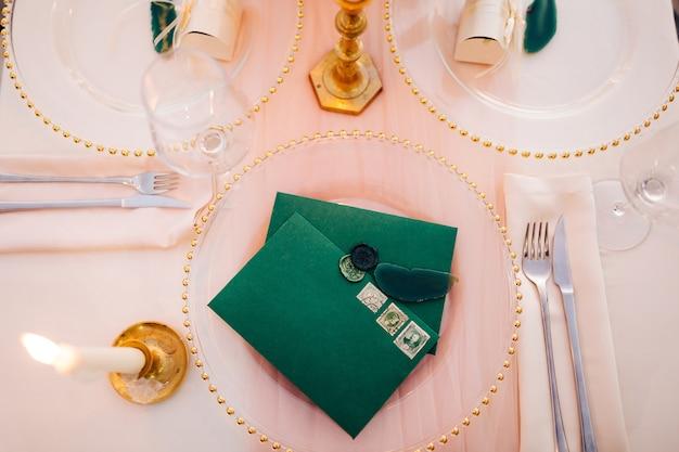 Leere grüne umschläge mit briefmarken liegen auf einem transparenten teller auf einem gedeckten tisch eine brennende kerze