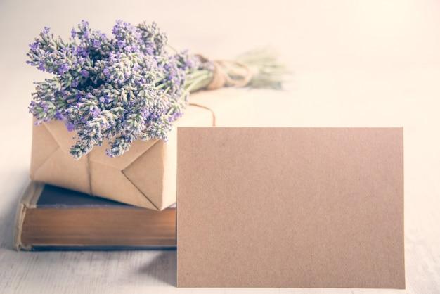 Leere gruß ktaft karte vor einem lavendelblumenstrauß, einem eingewickelten geschenk und einem alten buch über einem weißen hölzernen hintergrund.