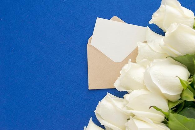 Leere grußkarte im offenen umschlag mit weißrose blüht auf blau