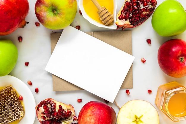 Leere grußkarte im rahmen aus honig, apfel und granatapfel