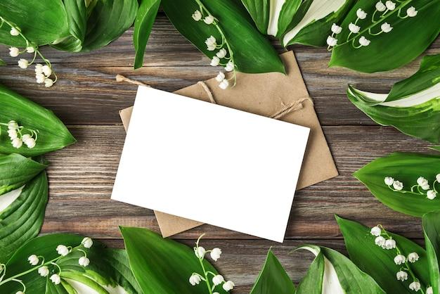 Leere grußkarte im rahmen aus maiglöckchenblumen auf rustikalem holz. draufsicht. flach liegen