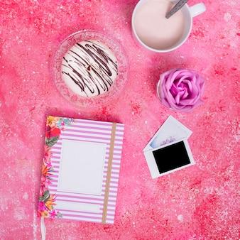 Leere grußkarte; krapfen; milch; rose und polaroid auf rosa strukturiertem hintergrund