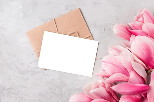 Leere grußkarte mit frühlingsrosa magnolienblüten. hochzeitseinladung. flach liegen