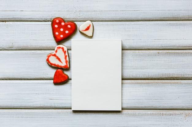 Leere grußkarte mit keksen in form des herzens. valentinstag konzept