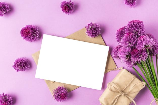 Leere grußkarte mit lila wildblumenstrauß, blumenköpfen und geschenkbox auf pastellpurpur. flach liegen