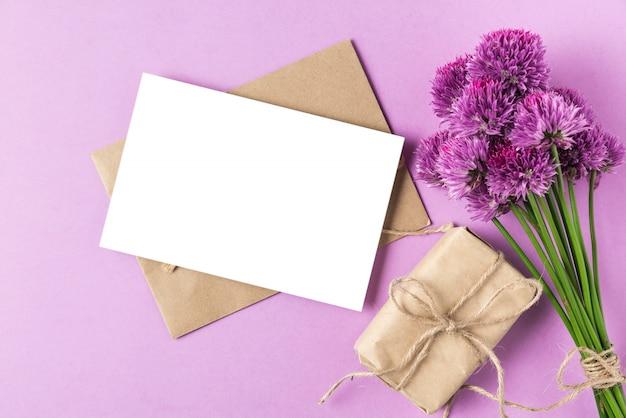 Leere grußkarte mit lila wildblumenstrauß oder zwiebelblumen und geschenkbox auf pastellpurpur