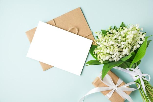 Leere grußkarte mit maiglöckchenblumenstrauß und geschenkbox auf blau. flach liegen