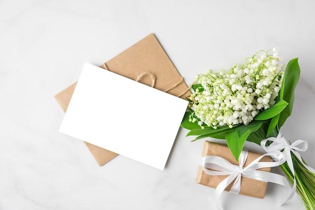 Leere grußkarte mit maiglöckchenblumenstrauß und geschenkbox auf weiß. flach liegen
