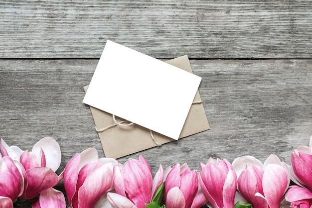 Leere grußkarte mit rosa magnolienblumen auf rustikalem holztisch. flach liegen. ansicht von oben