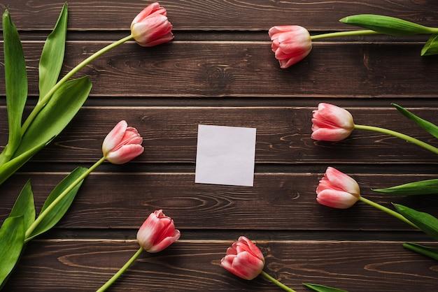 Leere grußkarte mit rosa tulpen und einem leeren aufkleber auf einem holztisch