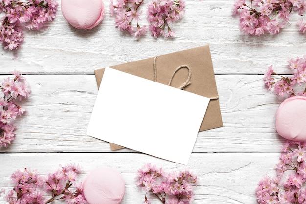 Leere grußkarte oder hochzeitseinladung im rahmen aus rosa kirschblüte oder sakura über weißem holztisch