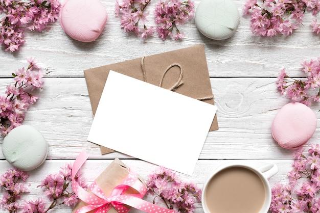 Leere grußkarte oder hochzeitseinladung im rahmen der rosa kirsche, die mit kaffeetasse und macarons blüht
