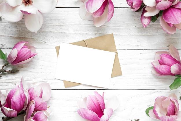 Leere grußkarte oder hochzeitseinladung im rahmen der rosa magnolienblüten