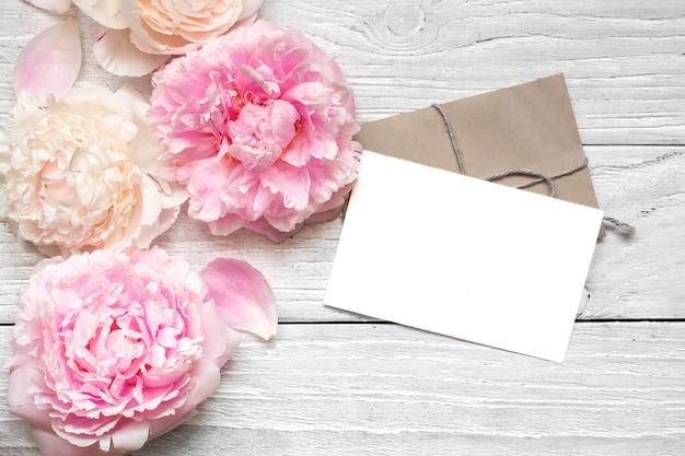 Leere grußkarte oder hochzeitseinladung mit rosa und cremigen pfingstrosenblumen über weißem holztisch.