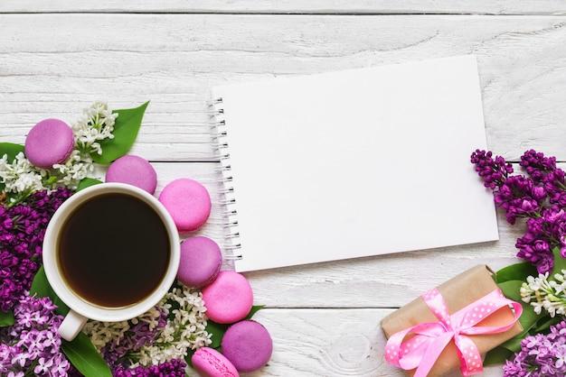 Leere grußkarte oder mit lila blumen, kaffeetasse, makronen und geschenkbox