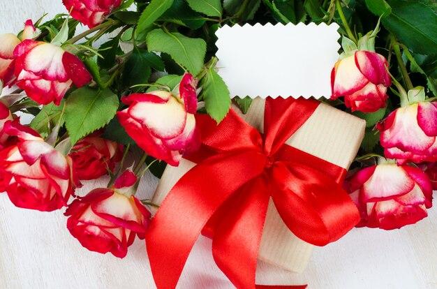 Leere grußkarte, rote rosen und geschenkbox