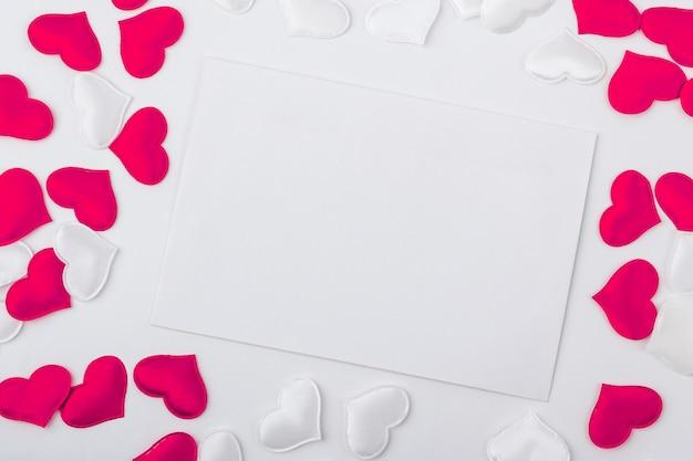Leere grußkarte und umschlag der schablone zur hochzeit. ein blatt papier unter den roten und weißen herzen. flache lage, kopieren sie platz für text