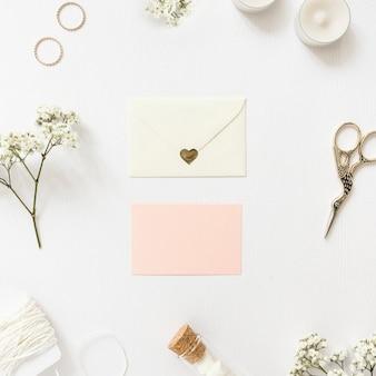 Leere grußkarten mit ringen umgeben; gypsophila; zeichenfolge; kerzen marshmallow reagenzglas und schere auf weißem hintergrund