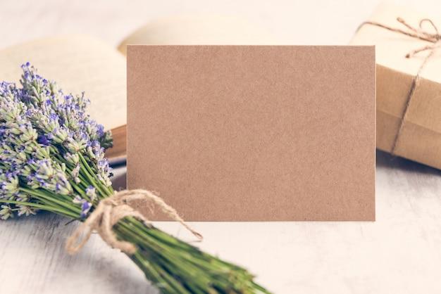 Leere grußkraftpapierkarte vor einem lavendelblumenstrauß, einem eingewickelten geschenk und einem alten buch über einem weißen hölzernen hintergrund.