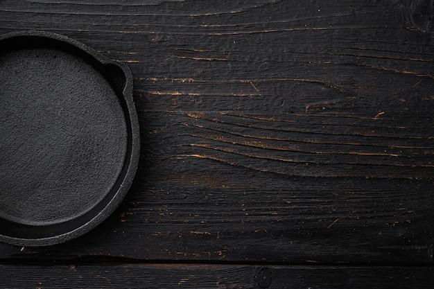 Leere gusseisenpfanne mit kopienraum für text oder essen mit kopienraum für text oder essen, draufsicht flach, auf schwarzem holztischhintergrund
