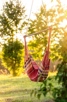 Leere hängematte im garten durch den baum in den sonnenuntergangslichtern, ruhe im freienkonzept