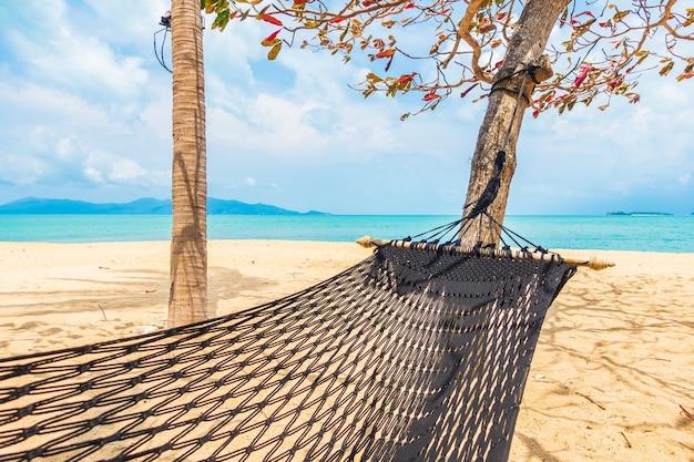 Leere hängematte schwingen um strandmeerozean mit weißem wolkenblauem himmel für reiseurlaub