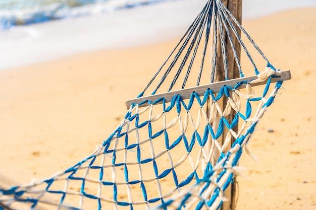Leere hängemattenschaukel auf dem schönen strand und dem meer