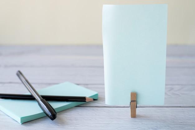 Leere haftnotiz mit wäscheklammerstapel aus buntem papierstift auf dem leeren stück des tisches
