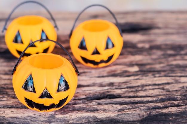 Leere halloween-kürbisgesichtseimer auf alter hölzerner beschaffenheit